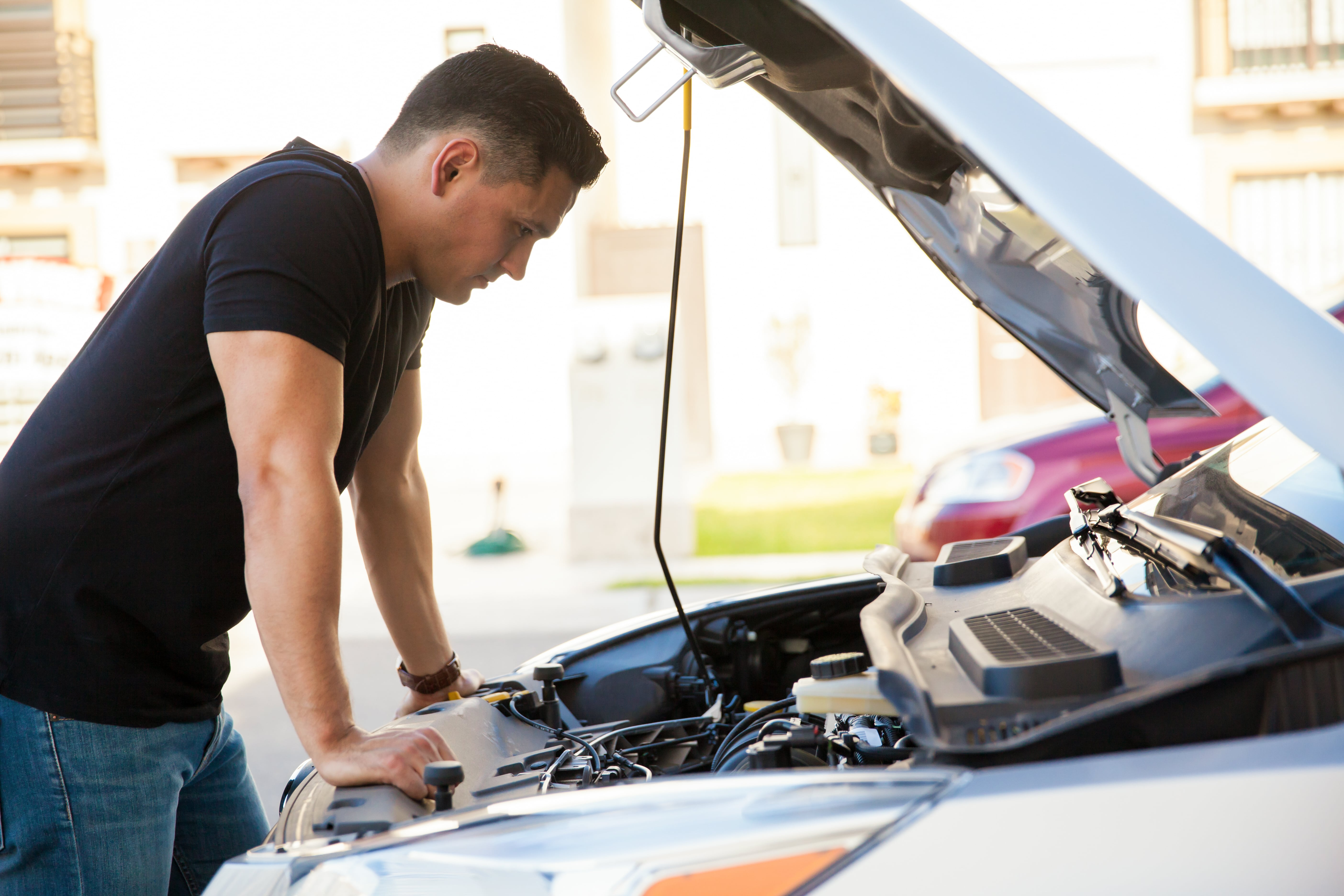 Young man looking at the engine of a broken down car.